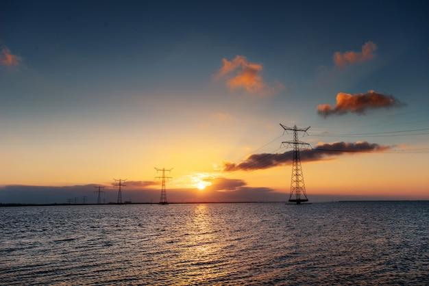 Elektrische leitung über wasser während eines fantastischen sonnenuntergangs