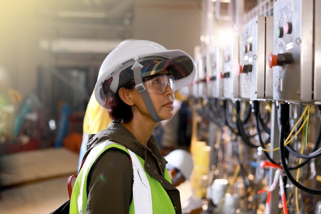 Elektrische steuerung der fraueningenieure mit schutzhelm und schutzbrille für industriegebiet oder kraftwerk