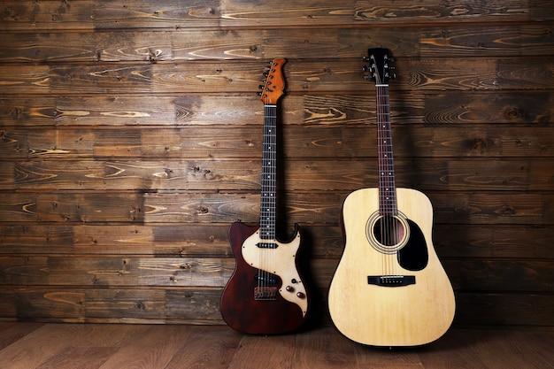 Elektrische und akustische gitarren auf hölzernem hintergrund