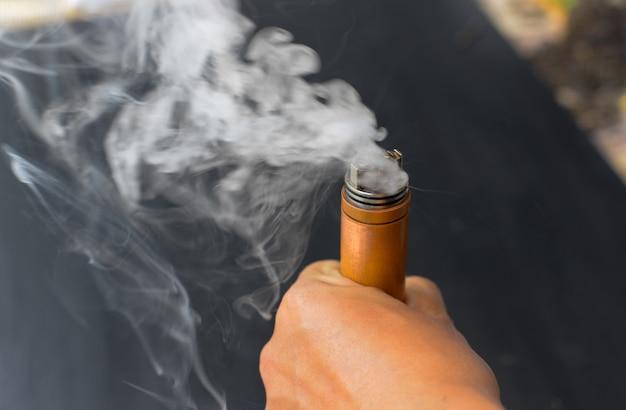 Elektrische zigarette, die in der hand mit weißem rauch, e-zigarette, varpo brennt.