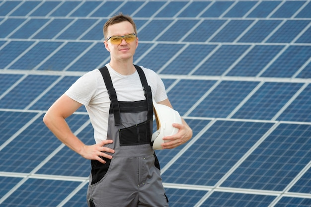 Elektrischer arbeiter, der weißen sicherheitshut hält und am kraftwerk steht. solaringenieur in gelben schutzgläsern und grauen overalls, die in der nähe des sonnenkollektorfeldes stehen.