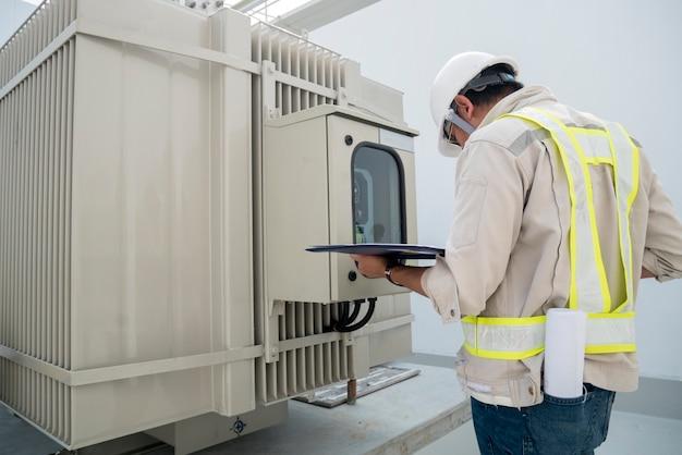 Elektrischer energietechniker überprüfen elektrischen transformator in der baustelle