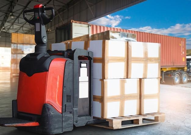 Elektrischer gabelstapler-palettenheber mit stapel von kartonschachteln auf der palette, die darauf warten, in containerwagen zu laden.