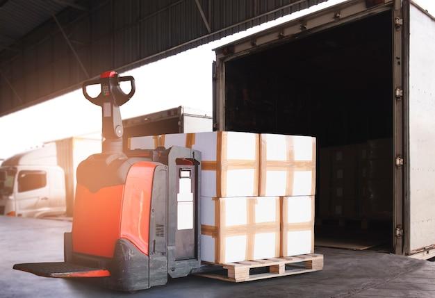 Elektrischer gabelstapler-palettenheber mit stapel von ladekisten, die in containerwagen entladen werden. frachtfracht per lkw.