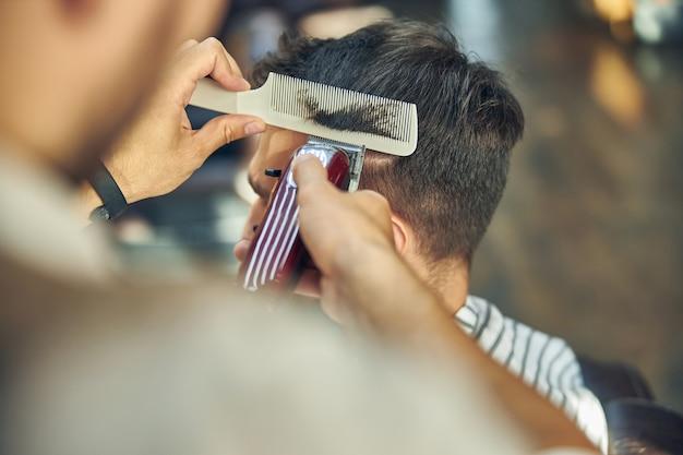 Elektrischer haarschneider, der verwendet wird, um einem jungen mann einen haarschnitt zu verpassen