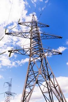 Elektrischer hochspannungsturm auf einem hintergrund des blauen himmels. leistungskonzept