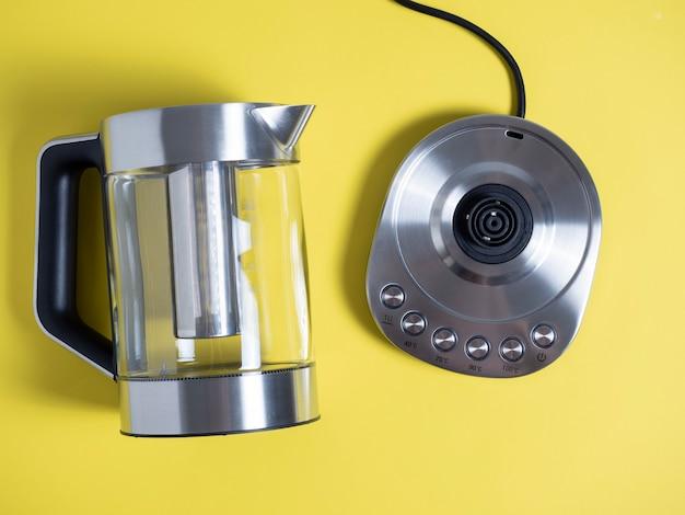 Elektrischer metallkessel in silberner farbe mit verschiedenen arten der wassererwärmung auf hellgelbem hintergrund. ansicht von oben, flach