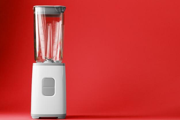 Elektrischer mixer mit einer leeren tasse auf einer roten oberfläche