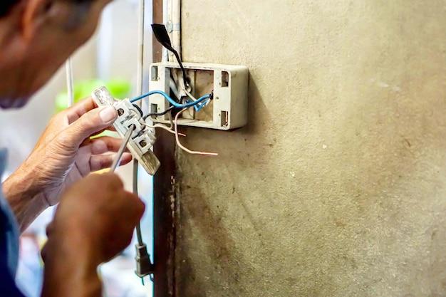 Elektrischer reparaturtechniker der nahaufnahme, der schraubenzieher hält und die steckdose auf altbauwand repariert.