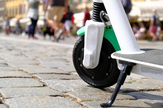 Elektrischer roller parkte auf pflasterung im alten stadtzentrum