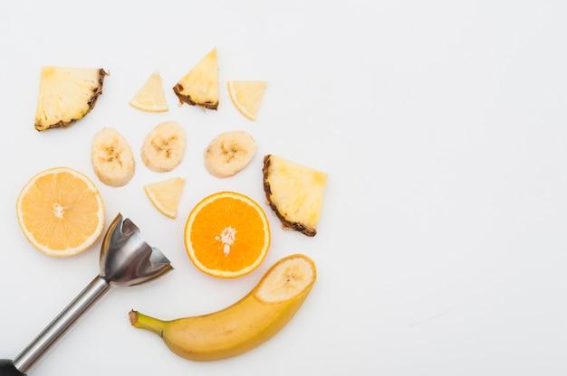 Elektrischer stabmixer aus edelstahl mit ananasscheiben; bananen- und orangenfrüchte auf weißem hintergrund