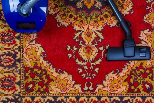 Elektrischer staubsauger auf dem hintergrund eines alten teppichs, draufsicht der ebenenlage