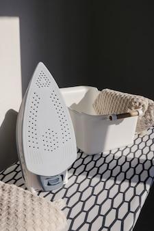 Elektrisches bügeleisen und ein stapel beiger handtücher in einem handtuchkorb auf bügelbrett in einem modernen waschraum