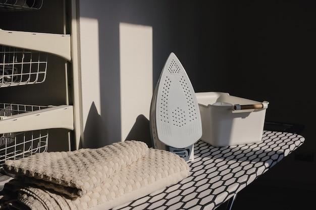 Elektrisches bügeleisen und handtuchhaufen auf bügelbrett im waschraum zu hause
