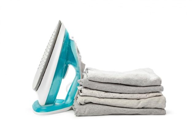 Elektrisches bügeleisen und kleiderstapel.