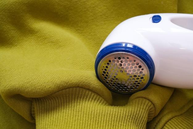 Elektrisches gerät zum entfernen von haaren und flusen in der stoffstruktur. rasierer für wolle. die maschine zum entfernen von pellets vor dem hintergrund eines strickpullovers.
