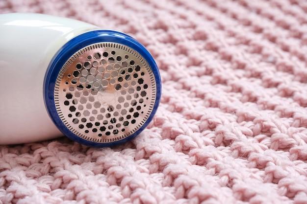 Elektrisches gerät zum entfernen von haaren und flusen in rosa stoffstruktur. rasierer für wolle