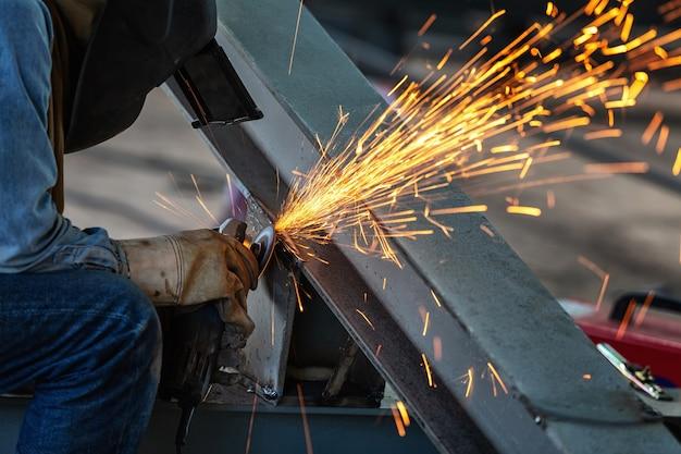 Elektrisches rad, das auf stahlstruktur und schweißer mit mehrfachen funken in der fabrik reibt.