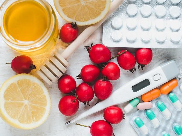 Elektrisches thermometer, pillen, frische gelbe zitrone, bank mit honig