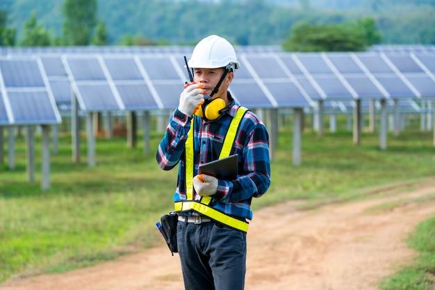 Elektrizitätssolartechnik, ingenieur, der solarpanel im routinebetrieb im solarkraftwerk überprüft.