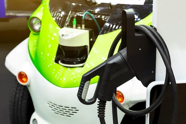 Elektroauto, das auf parkplatz mit ladestation des elektroautos auf stadtstraße auflädt.