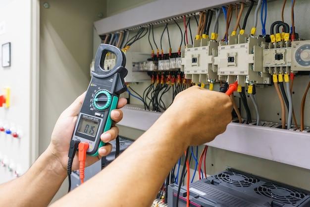 Elektroingenieur justiert elektrische ausrüstung mit einem multimeterprüfgerät in seiner hand