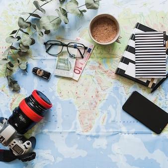 Elektronische ausrüstung, euro-banknoten, kaffee und notizbuch über der karte