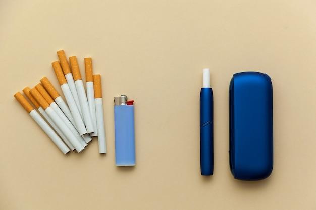 Elektronische blaue iqos-zigarette gewöhnliche zigaretten mit einem feuerzeug auf beigem hintergrund