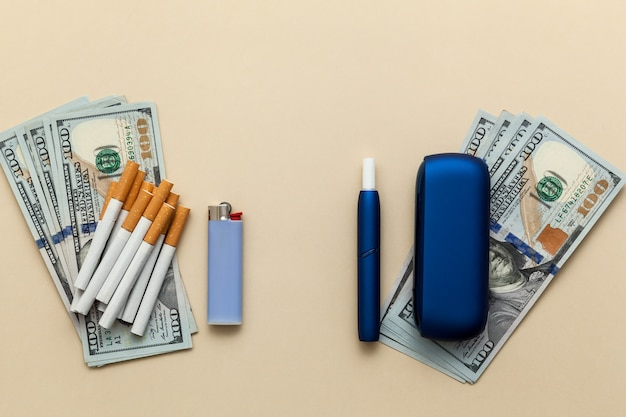 Elektronische blaue iqos-zigarette gewöhnliche zigaretten mit feuerzeug und geld auf beigem hintergrund
