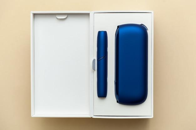 Elektronische blaue iqos-zigarette in einer weißen schachtel auf beigem hintergrund