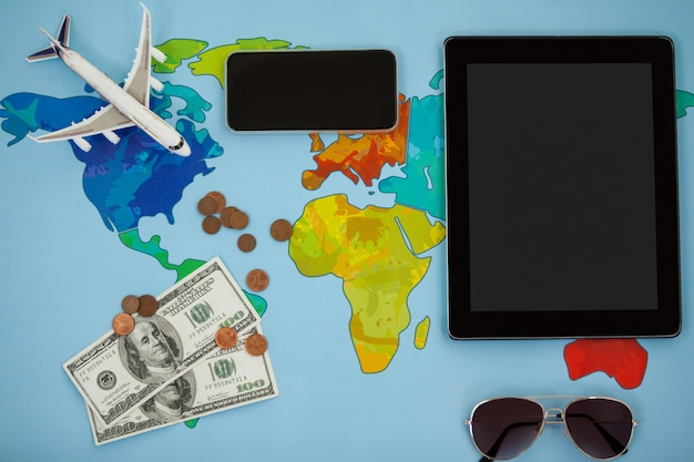Elektronische geräte, sonnenbrillen, dollar und flugzeugmodell