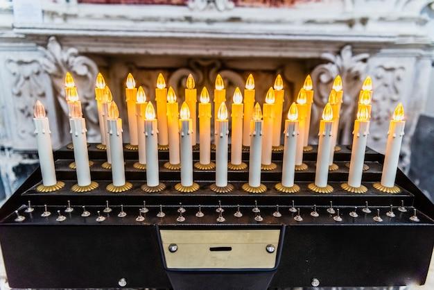 Elektronische kerzen mit leds in einer kirche, um ein almosenangebot zu machen.