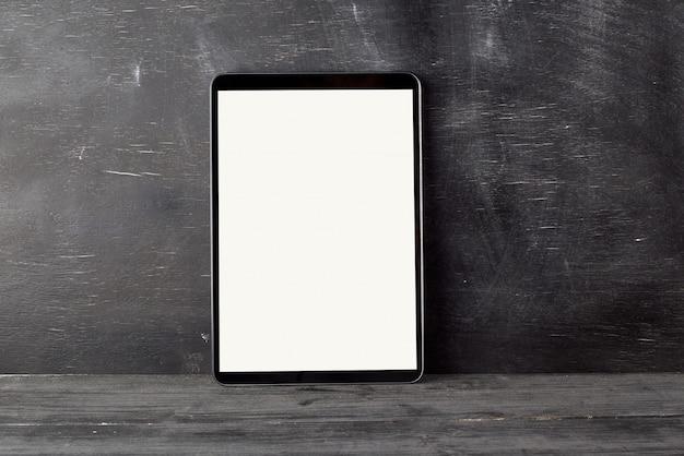 Elektronische tablette mit einem leeren weißen bildschirm gegen ein schwarzes kreidebrett