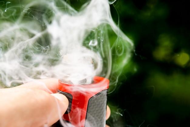 Elektronische zigarette stößt sichtbare spiralwolle und dampf aus.