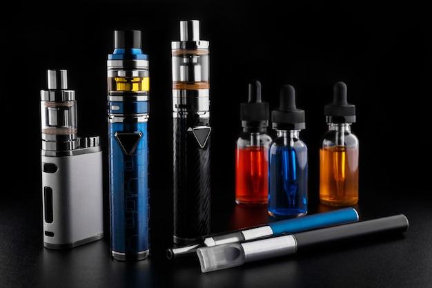 Elektronische zigaretten und flaschen mit dampfflüssigkeit auf schwarzem hintergrund