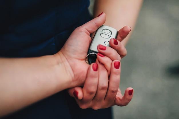 Elektronischer autoschlüssel in den händen einer frau