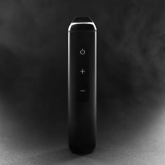Elektronischer zigarettenverdampferstift auf rauchiger dunkler oberfläche