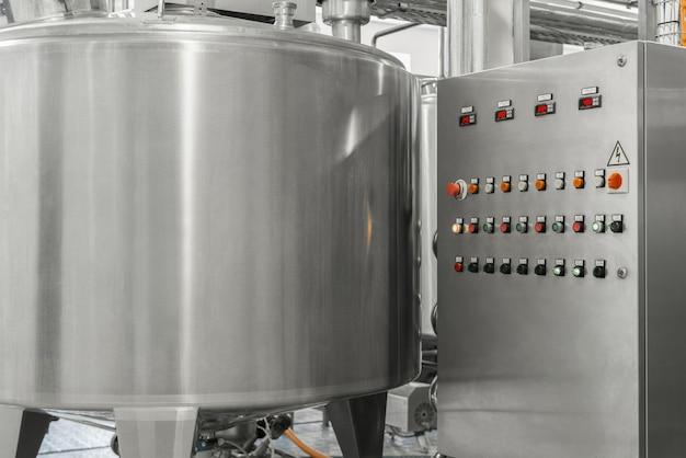 Elektronisches bedienfeld und tank in einer milchfabrik. ausrüstung in der molkerei
