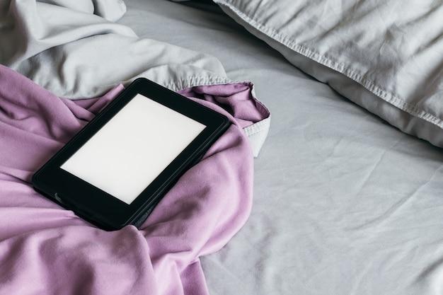 Elektronisches buch mit einem leeren bildschirm auf einem grauen und lila bett