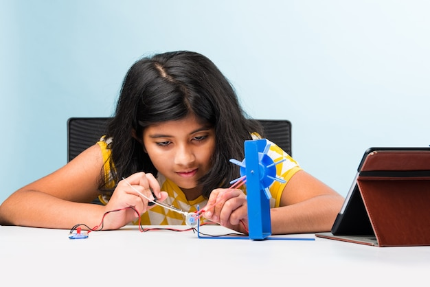 Elektronisches experiment - asiatische indische kleine studentin, die windmühlenforschung mit drähten, verbindungen durchführt, von laptop oder tablet-computer lernt
