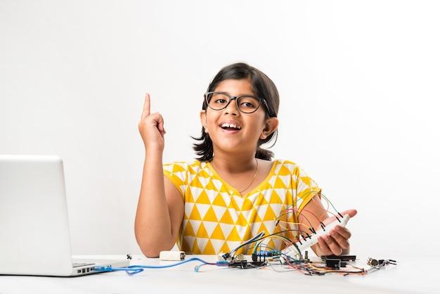 Elektronisches experiment - asiatische indische kleine studentin, die wissenschaft mit drähten, verbindungen durchführt oder studiert, von laptop oder tablet-computer lernt