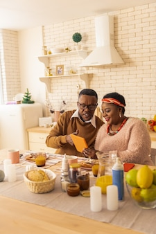 Elektronisches gerät. erfreut nette brüder und schwestern, die auf das tablet schauen, während sie in der küche sind
