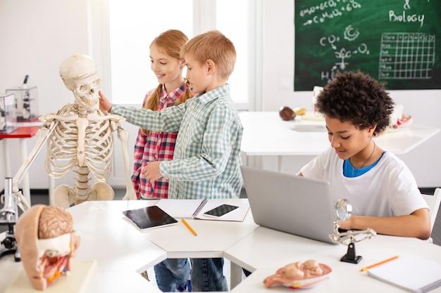Elektronisches lernen. schlauer junge, der am laptop sitzt, während er biologie studiert