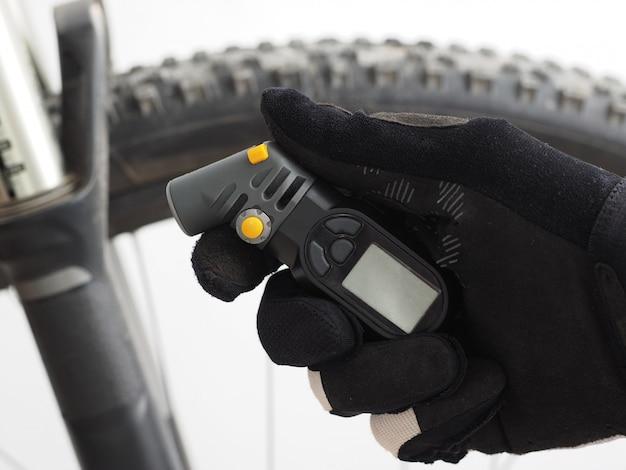 Elektronisches manometer zur messung des fahrradreifendrucks in der hand eines männlichen radfahrers.