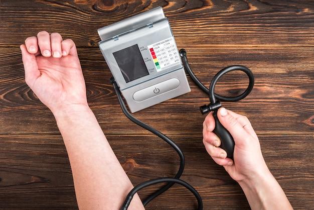 Elektronisches medizinisches tonometer zur messung des blutdrucks auf holztisch