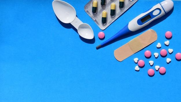 Elektronisches thermometer, pillen oder vitamine an einer blauen wand.
