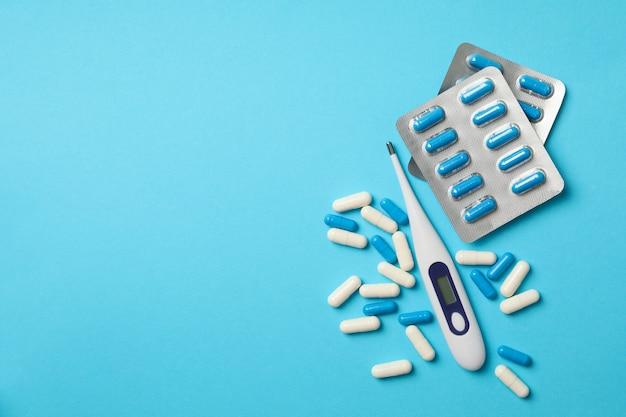 Elektronisches thermometer und pillen auf blau