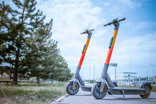 Elektroroller in reihe auf dem parkplatz. city-bike-verleihsystem, öffentliche tretroller auf der straße
