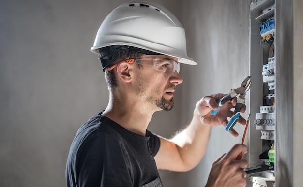 Elektrotechniker, der in einer schalttafel mit sicherungen arbeitet