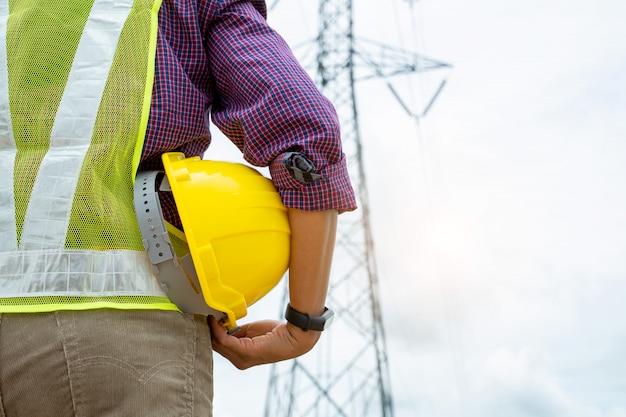Elektrotechniker, der schutzhelm hält, der an elektrischer energie arbeitet.